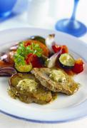 Pork steaks with herb butter and vegetable accompaniments Stock Photos