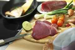 Tuna steak with vegetables and lime on wooden board Stock Photos