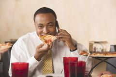 Businessman eating pizza & making phone call in restaurant Stock Photos