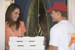 Young woman at house door receiving a pizza delivery Stock Photos