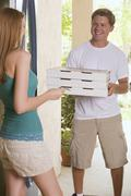Young woman at house door receiving pizza delivery Stock Photos