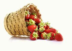 Fresh strawberries falling out of a basket Stock Photos