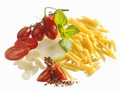Ingredients for pasta dish (penne, tomatoes, onion, basil) Stock Photos