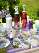 Cups, glasses, drinks & purple lilac on table out of doors Stock Photos