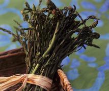 A bundle of green asparagus in a basket Stock Photos