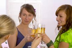 Young women clinking glasses of champagne Stock Photos