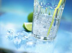 A glass of mineral water with straw, crushed ice and lime Stock Photos