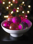 Bowl of Christmas baubles, Christmas tree in background Stock Photos