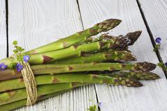 A bundle of green asparagus on white wood Stock Photos