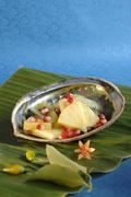 Pineapple, kiwi fruit & pomegranate seeds in abalone shell Stock Photos