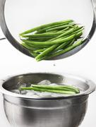 Blanched beans being quenched in iced water Stock Photos