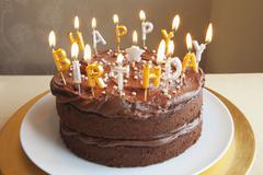 A chocolate birthday cake with lots of candles Stock Photos
