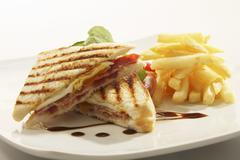 Toasted egg and bacon sandwich with chips Stock Photos
