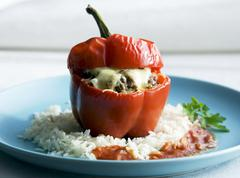 A pepper stuffed with minced meat and cheese on a bed of rice Stock Photos