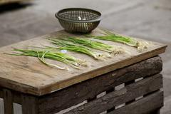 Spring onions lying on a rustic wooden table Stock Photos