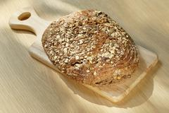 Wholemeal bread on a small wooden board Stock Photos
