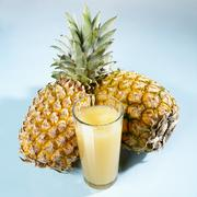 A glass of pineapple juice in front of two whole pineapples Stock Photos