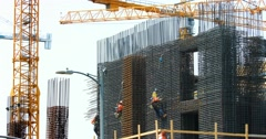 Construction workers and crane install metal frame at development site, 4K, RAW Stock Footage