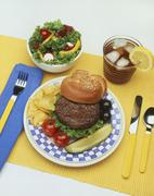 Hamburger with Pickle and Chips; Side Salad and Iced Tea Stock Photos