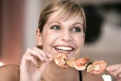Young woman with shrimp kebab in her hand Stock Photos