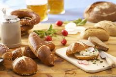 Still life with bread, rolls, beer and radishes Stock Photos