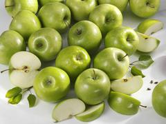 Granny Smith' apples, whole and cut into pieces Stock Photos