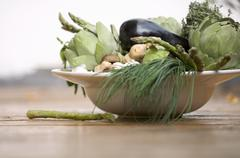 Bowl of vegetables: artichokes, aubergines, chives etc. Stock Photos