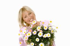 Cheerful woman holding bouquet of marguerites in her hands Stock Photos