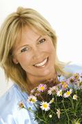 Woman holding bouquet of marguerites in her hands Stock Photos