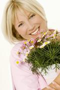 Woman with pot of marguerites in her hands Stock Photos