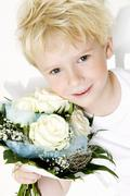 Blond boy holding bouquet of white roses in his hands Stock Photos