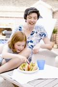 Woman and small girl with two hot dogs Stock Photos