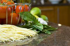 Tomatoes in wire basket with pasta and herbs Stock Photos