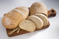 Whole and partly sliced loaves of bread on a wooden board Stock Photos