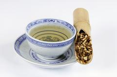 Bowl of tea with hare's ear root in a bamboo cane Stock Photos
