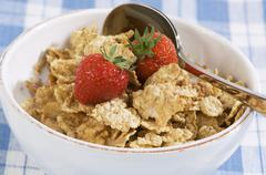 Bowl of wholemeal cornflakes and fresh strawberries Stock Photos
