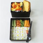Sushi, vegetables, fruit salad and cake in bento boxes Stock Photos