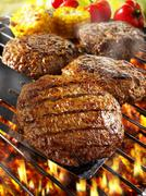 Burgers on barbecue rack and on spatula Stock Photos