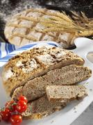 Rustic bacon bread, partly sliced Stock Photos