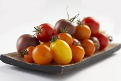 Tomatoes of various colours on wooden plate Stock Photos