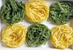 Green and yellow ribbon pasta nests (overhead view) Stock Photos