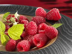 Raspberries with leaf in wooden bowl Stock Photos