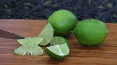Lime Being Cut on a Wooden Cutting Board. Stock Footage