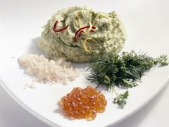 Avocado puree with herbs, shallots and trout caviar Stock Photos