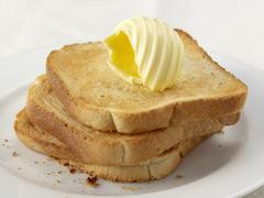 Three slices of toast with butter curl Stock Photos