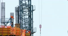Construction workers and crane install metal frame at development site 4K RAW Stock Footage