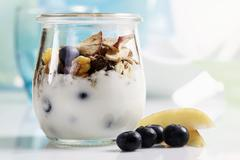 Yoghurt with muesli, blueberries and dried fruit Stock Photos