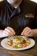Chef Placing Chive Garnish on Fish Entree Stock Photos