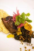 Maple Soaked Angus Beef Tenderloin on Jalapeno Grits and Greens Stock Photos