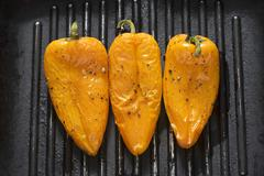 Three yellow peppers in a grill frying pan Stock Photos